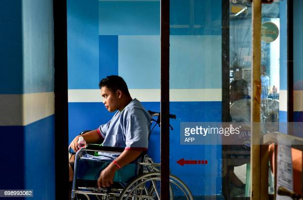 This photo taken on June 20 shows a soldier on a wheelchair looking by the window while he is being treated from war injuries inflicted during combat...