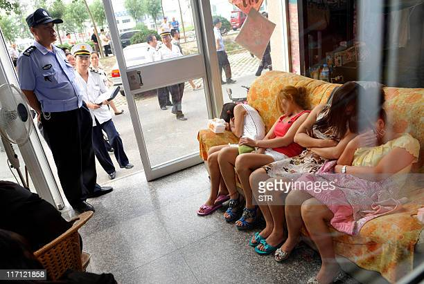 This photo taken on June 21 2011 shows Chinese police watching over a group of massage girls suspected of prostitution during a raid on a parlour in...