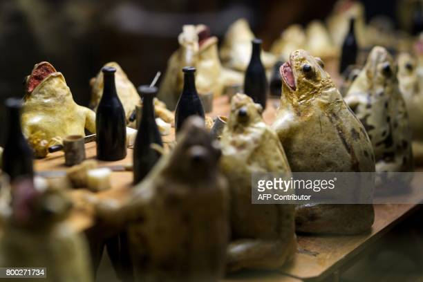This photo taken on June 22 2017 shows models of frogs attending a banquet at the Frog Museum in EstavayerleLac western Switzerland The museum shows...