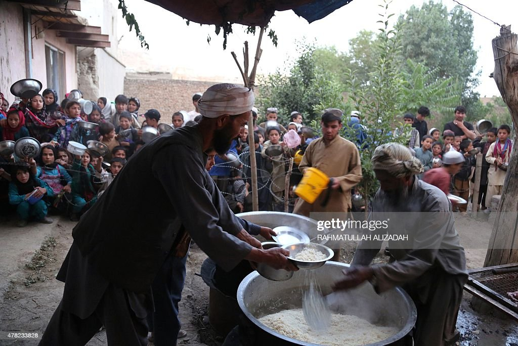 This photo taken on June 23, 2015 shows Afghan men distributing food during the holy month of Ramadan in Ghazni. Across the Muslim world, the faithful fast from dawn to dusk and strive to be more pious during the holy month, which ends with the Eid holiday. AFP PHOTO / Rahmatullah Alizadah