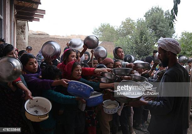 This photo taken on June 23 2015 shows Afghan men distributing food during the holy month of Ramadan in Ghazni Across the Muslim world the faithful...