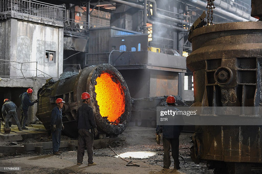 This photo taken on June 25, 2011 shows employees working beside a giant cauldron at a steel mill in Hefei, in eastern China's Anhui province. Growth in China's manufacturing activity fell to an 11-month low in June, preliminary HSBC data released on June 23 showed, as Beijing's efforts to cool the red-hot economy continued to bite. CHINA