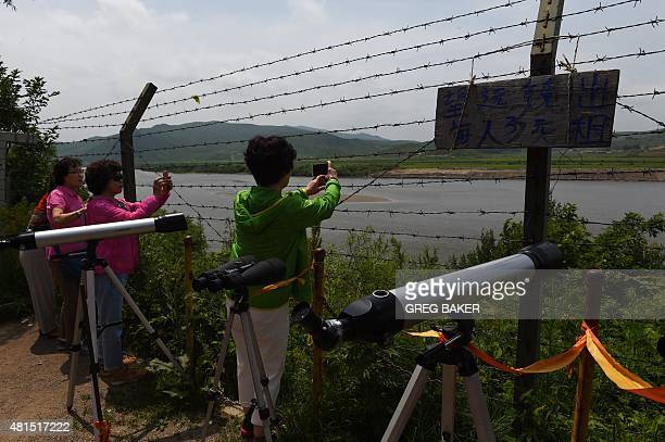 STORY 'CHINANKOREARUSSIAECONOMYDIPLOMACY' FOCUS This photo taken on June 25 2015 shows South Korean tourists taking photos of North Korea across the...