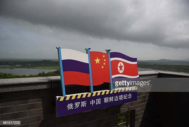 STORY 'CHINANKOREARUSSIAECONOMYDIPLOMACY' FOCUS This photo taken on June 25 2015 shows the flags of Russia China and North Korea on a viewing tower...