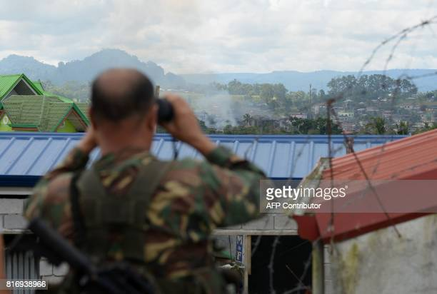 This photo taken on June 26 2017 shows a soldier using binoculars to look at smoke billowing from a burning houses after aerial bombings on Muslim...