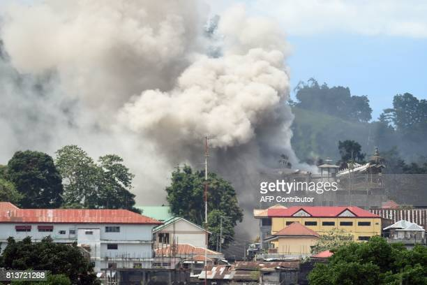 This photo taken on June 26 2017 shows smoke billowing from a building following an bombing run against militant Islamist positions by a Philippine...