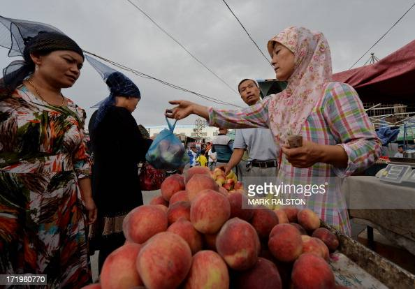 This photo taken on June 27 2013 shows Uighur traders at the main bazaar in Turpan Xinjiang region Riots in China's ethnically divided Xinjiang...