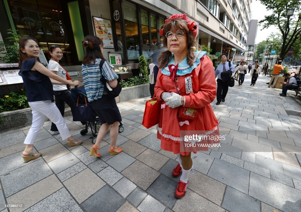 This photo taken on June 27, shows Yuzo Shiozawa (C) a 60 year old Tokyoite dressed in a hand-made costume of cartoon heroine Candy walking on a street at Harajuku fashion district in Tokyo. Candice 'Candy' White Ardlay is the main character of a hugely popular cartoon anime series originally launched in Japan in the 1970s and set in the United States during the early 20th century. AFP PHOTO / Toru YAMANAKA