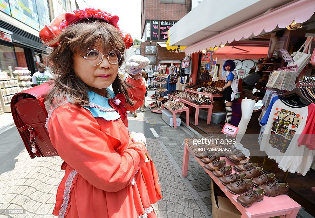 This photo taken on June 27, shows Yuzo Shiozawa (C) a 60 year old Tokyoite dressed in a hand-made costume of cartoon heroine Candy posing on a street at Harajuku fashion district in Tokyo. Candice 'Candy' White Ardlay is the main character of a hugely popular cartoon anime series originally launched in Japan in the 1970s and set in the United States during the early 20th century. AFP PHOTO / Toru YAMANAKA