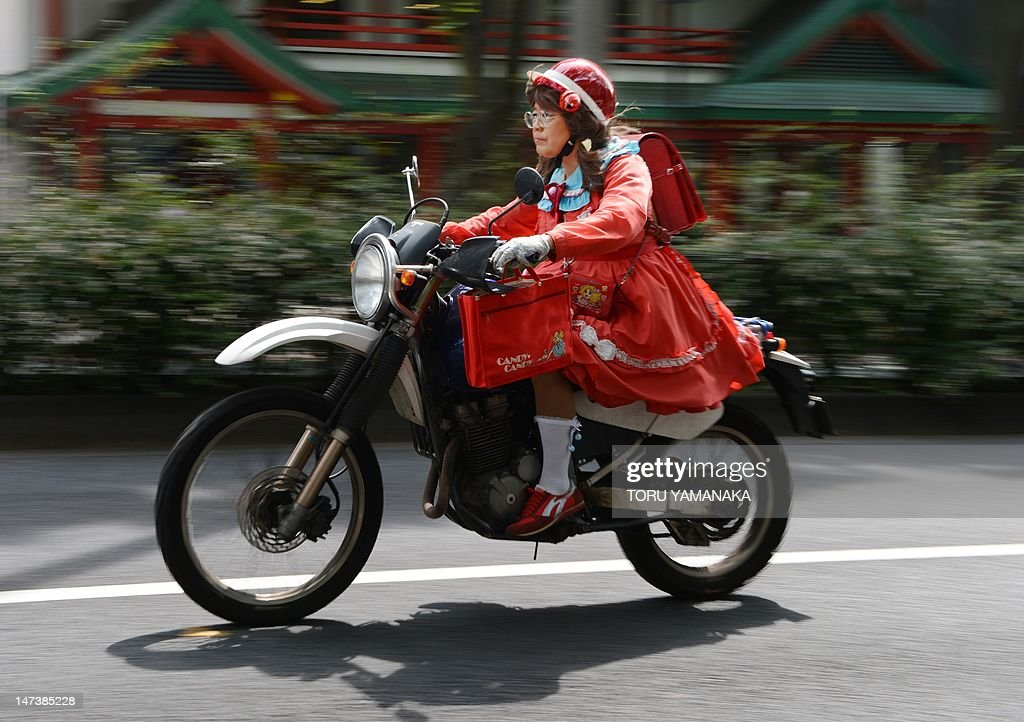 This photo taken on June 27, shows Yuzo Shiozawa (C) a 60 year old Tokyoite dressed in a hand-made costume of cartoon heroine Candy riding a 250-cc Suzuki motorbike at Harajuku fashion district in Tokyo. Candice 'Candy' White Ardlay is the main character of a hugely popular cartoon anime series originally launched in Japan in the 1970s and set in the United States during the early 20th century. AFP PHOTO / Toru YAMANAKA