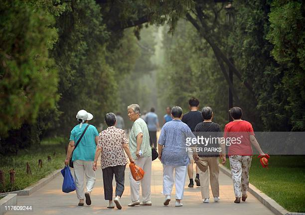 This photo taken on June 28 2011 shows elderly women heading for their early morning exercises in Ditan Park in Beijing China's population is ageing...