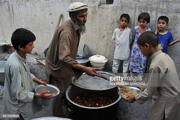 This photo taken on June 30 2014 shows Afghan children receiving food donated by a private charity as they prepare to break their fast during the...