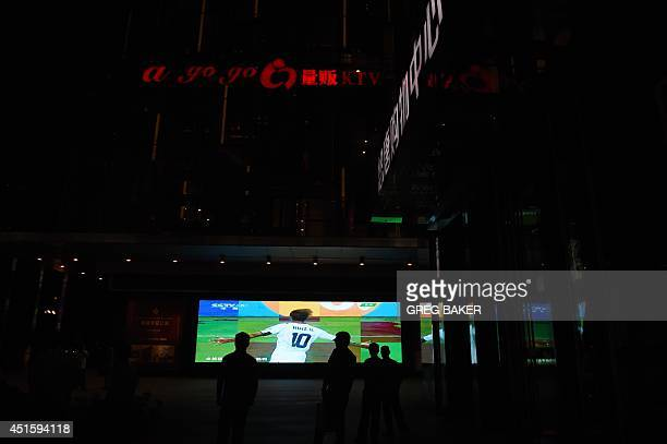 This photo taken on June 30 2014 shows Chinese fans watching a replay of Costa Rica's Bryan Ruiz celebrating a goal during the World Cup match...