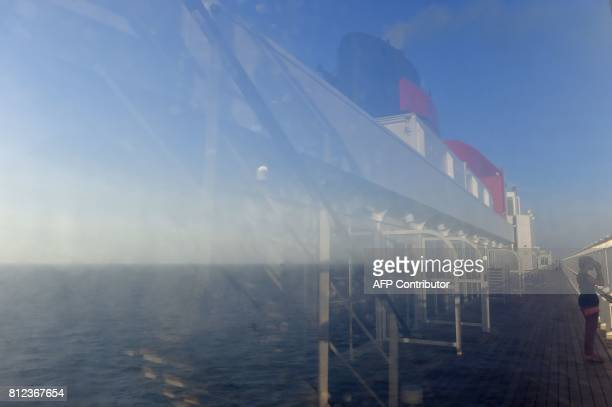 This photo taken on June 30 2017 shows the reflection on a window of a passenger looking out from the deck of the Cunard cruise liner RMS Queen Mary...
