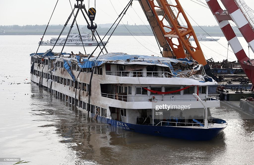 This photo taken on June 5 2015 shows cranes raising the sank ship 'Eastern Star' at the disaster site in Jianli central China's Hubei province A...