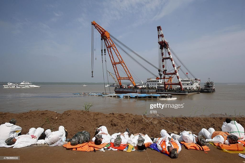 This photo taken on June 5 2015 shows rescuers sleeping on the nearby ground as cranes raise the sunken ship 'Eastern Star' at the disaster site in...