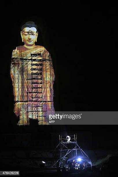 This photo taken on June 7 2015 shows the projected image of a Buddha statue in Bamiyan that had been destroyed by the Taliban in 2001 The initiative...