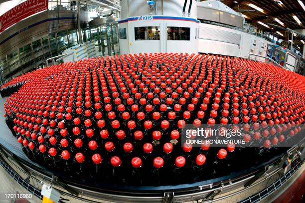 This photo taken on June 7 in Clamart near Paris shows newly produced CocaCola soft drink bottles on an assembly line at a Coca Cola bottling plant...