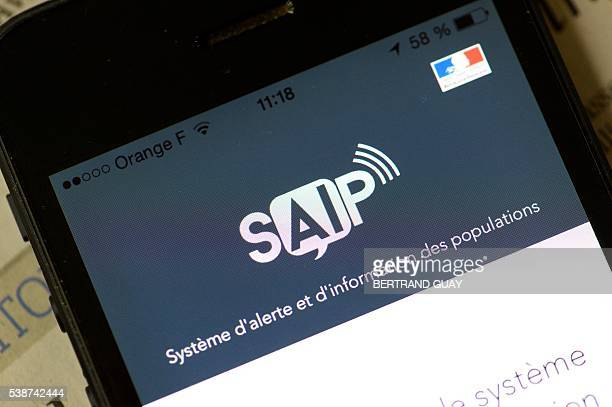 This photo taken on June 8 2016 shows A smartphone with the logo of the SAIP a new smartphone app designed to alert users to possible terror attacks...