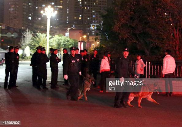 This photo taken on March 1 2014 shows police investigators inspecting the scene on a street outside the Kunming railway station after an attack in...
