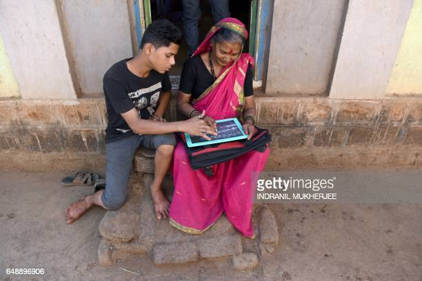 This photo taken on March 1 2017 shows Aniket Kedar helping his grandmother Gulab Kedar complete her homework at the Aajibaichi Shala or 'school for...