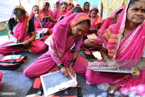 This photo taken on March 1 2017 shows Indian grandmother Draupada Kedar and other classmates attending a class at Aajibaichi Shala or 'school for...