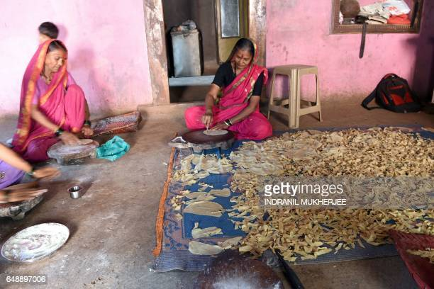 This photo taken on March 1 2017 shows Indian grandmother Draupada Kedar and Gulab Kedar making papads at home after attending class at Aajibaichi...