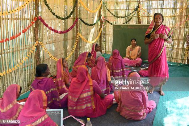This photo taken on March 1 2017 shows Indian grandmother Gulab Kedar introducing herself to her classmates as they wait for the start of a class at...