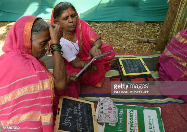 This photo taken on March 1 2017 shows Indian grandmother Kantabai More explaining a lesson to her classmate Sulochona Kedar during a class at...