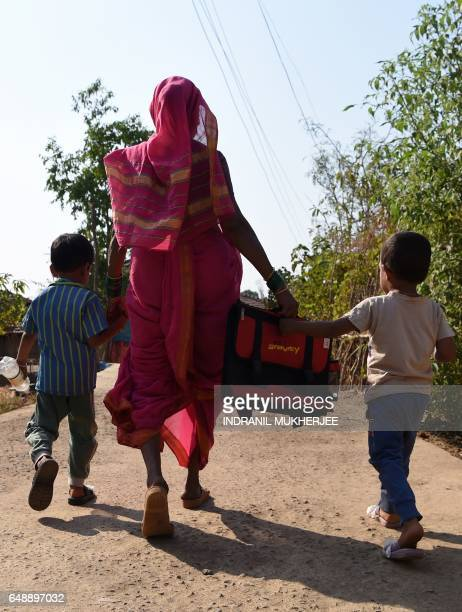 This photo taken on March 1 2017 shows Indian grandmother Savita Kedar being accompanied by her grandchildren as she walks home from Aajjibaichi...