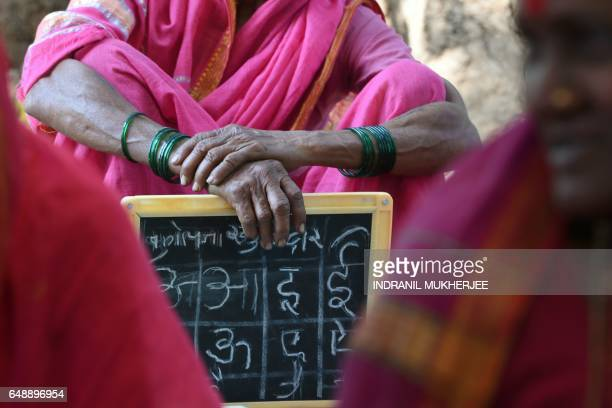 TOPSHOT This photo taken on March 1 2017 shows Indian grandmother Sulochona Kedar waiting to show her homework to the teacher at the Aajibaichi Shala...