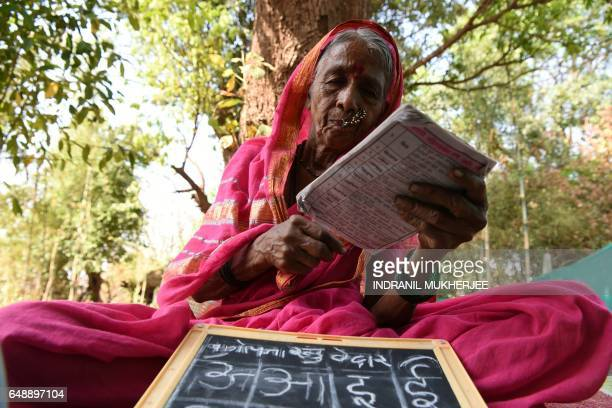 This photo taken on March 1 2017 shows Indian grandmother Sulochona Kedar reading from a textbook during a class at Aajibaichi Shala or 'school for...