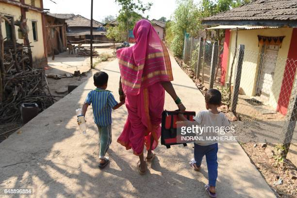 This photo taken on March 1 2017 shows Savita Kedar being accompanied by her grandchildren as she walks home after attending class at the Aajibaichi...