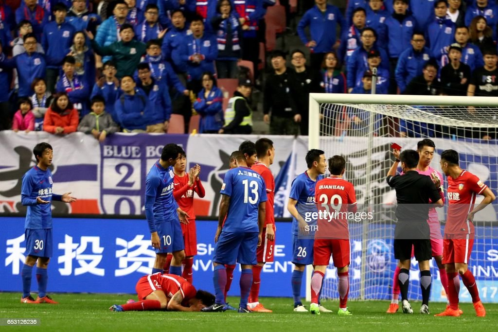This photo taken on March 11, 2017 shows Shanghai Shenhua's Qin Sheng (26) receiving a red card during the Chinese Super League match against Tianjin Quanjian in Shanghai. Shanghai Shenhua will withhold the salary of China international Qin Sheng for the rest of the season after condemning the midfielder's 'abominable behaviour' in stamping on Belgium's Axel Witsel at the weekend. / AFP PHOTO / STR / China OUT