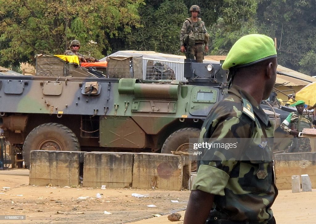 This photo taken on March 13, 2014 shows a Cameroonian customs officer (Front) standing on the Cameroon side looking at a French armored vehicle part of the Sangaris operations, parked on the Centrafrican side of the frontier post of Garoua-Boulai, eastern Cameroon, strategically located on the axis linking Bangui to Cameroon. Trade traffic resumed mid-March 2014 between Cameroon and the Central African Republic, with convoys escorted by the French army, although the Cameroonian drivers still fear the violence tearing entire regions on the road to Bangui.