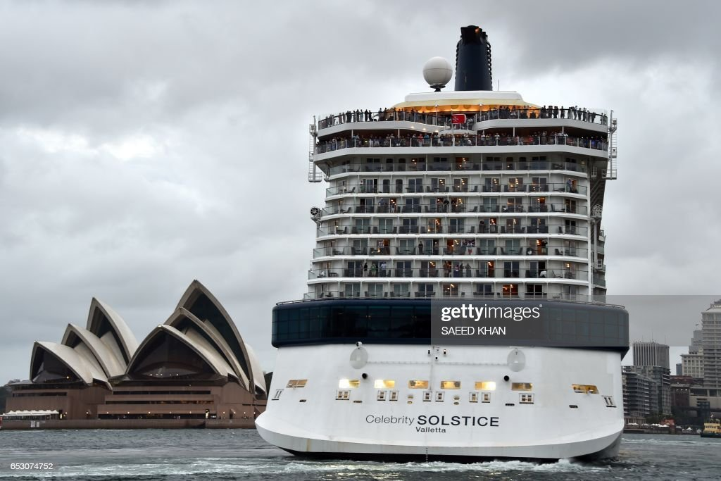 This photo taken on March 13, 2017 shows a cruise ship leaving Sydney harbour as storm clouds cover the sky. / AFP PHOTO / Saeed KHAN