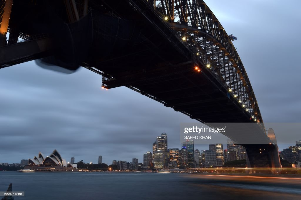 This photo taken on March 13, 2017 shows dark clouds covering the sky over Sydney harbour. A severe weather warning remained on the second day throughout the New South Wales with thunderstorms and heavy rainfall forecast. / AFP PHOTO / Saeed KHAN