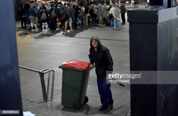 This photo taken on March 15 2017 shows a man pushing a bin as homeless people queue for food from a charity van outside a makeshift shelter for the...