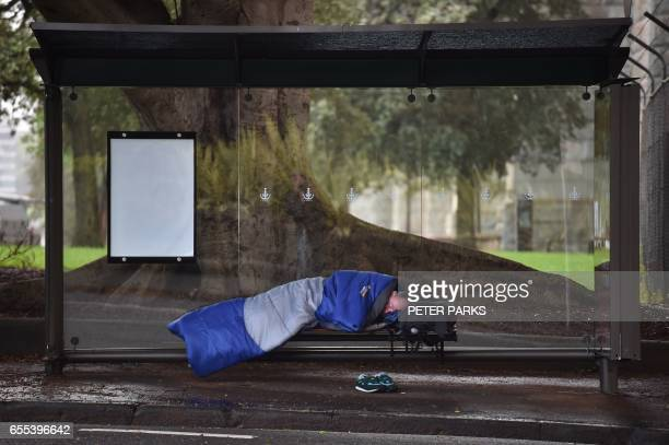 TOPSHOT This photo taken on March 17 2017 shows a man sleeping in a bus shelter near Sydney harbour in Sydney Homelessness is on the rise in...
