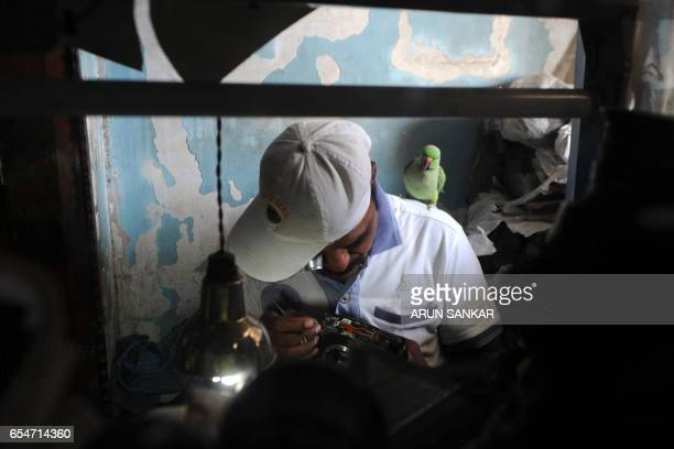 This photo taken on March 17 2017 shows Indian camera technician and parakeet enthusiast Joseph Sekar repairing a camera with a parakeet on his...