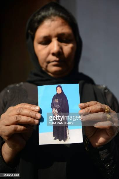 This photo taken on March 17 2017 shows Wahidaben Nasirkhan Pathan in Ahmedabad holding a photo of her sister Hafijabanu Rajabhusen who has been...