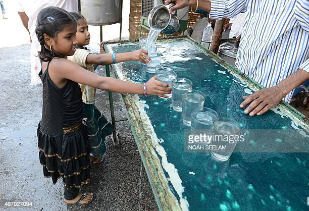 This photo taken on March 18 2015 shows girls getting a glass of water at a free drinking water distribution stand in Hyderabad A new UN report...