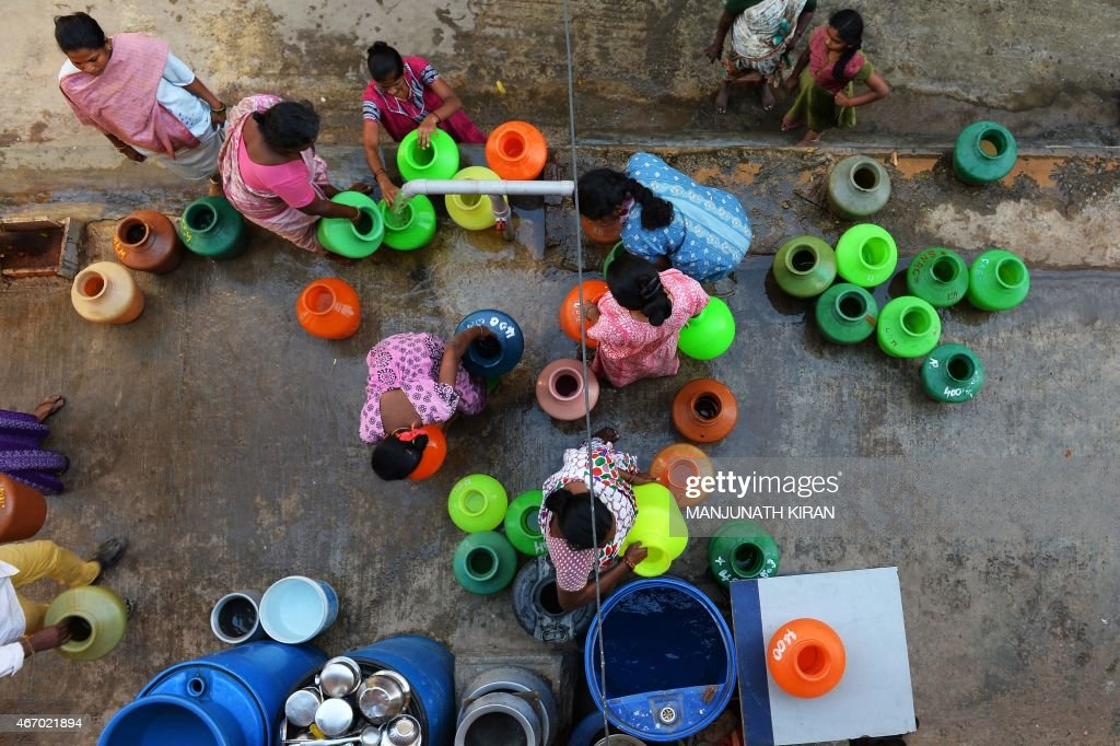 This photo taken on March 18 2015 shows residents in Bangalore waiting to collect drinking water in plastic pots from a community tap A new UN report...