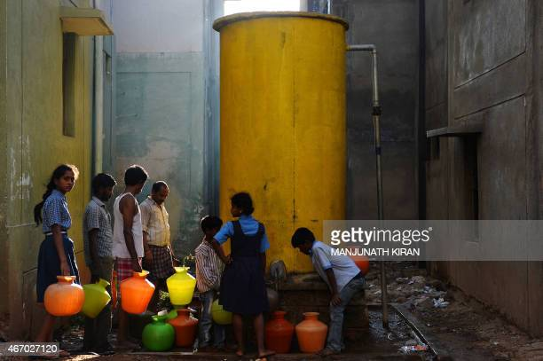 This photo taken on March 18 2015 shows residents of Bangalore who face water shortages carrying drinking water in plastic pots to their households A...