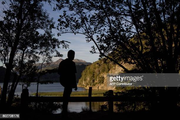 This photo taken on March 19 2010 shows a man watching the Arrayanes river and Verde lake at Los Alerces national park in the Patagonian province of...