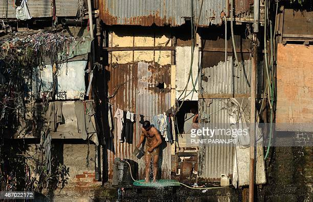 This photo taken on March 19 2015 shows an Indian man bathing in an open area at Dharavi in Mumbai A new UN report launched in New Delhi on March 20...