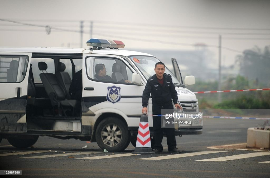 This photo taken on March 2, 2013 shows a police roadblock on the main road to the village of Shangpu in China's southern Guangdong province. Villagers in southern China were locked in a stand-off with authorities on March 3 and were demanding democratic polls after a violent clash with thugs linked to a local official over a land transfer. Just over a week ago, residents of Shangpu in Guangdong province fought with scores of attackers whom they claimed were sent by the village communist party chief and a business tycoon after they protested against a land deal. AFP PHOTO / Peter PARKS