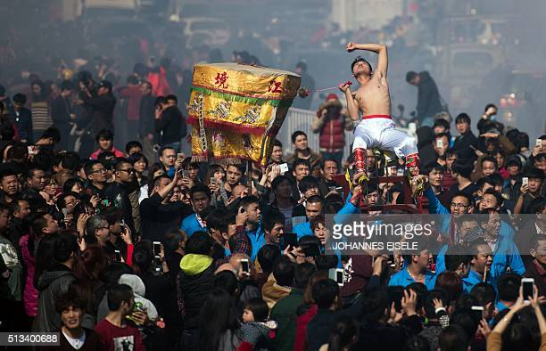 This photo taken on March 2 2016 shows a young man flaying his back with a thorny iron during the 'Da Tiequ' event in the village of Zheqiancun in...