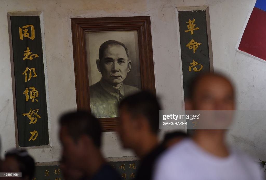 BLANC This photo taken on March 20, 2015 shows visitors walking past a portrait of Kuomintang founder Sun Yat-sen at the National Martyrs Cemetary at Tengchong, in China's southwest Yunnan province. The cemetary contains the remains of Kuomintang soldiers who fought against Japan during World War II. AFP PHOTO / Greg BAKER