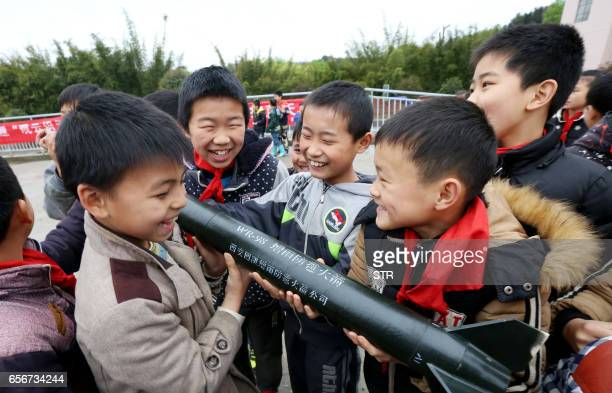 This photo taken on March 22 2017 shows Chinese students holding a model of a rainfallenhancement and antihail rocket during a meteorological...